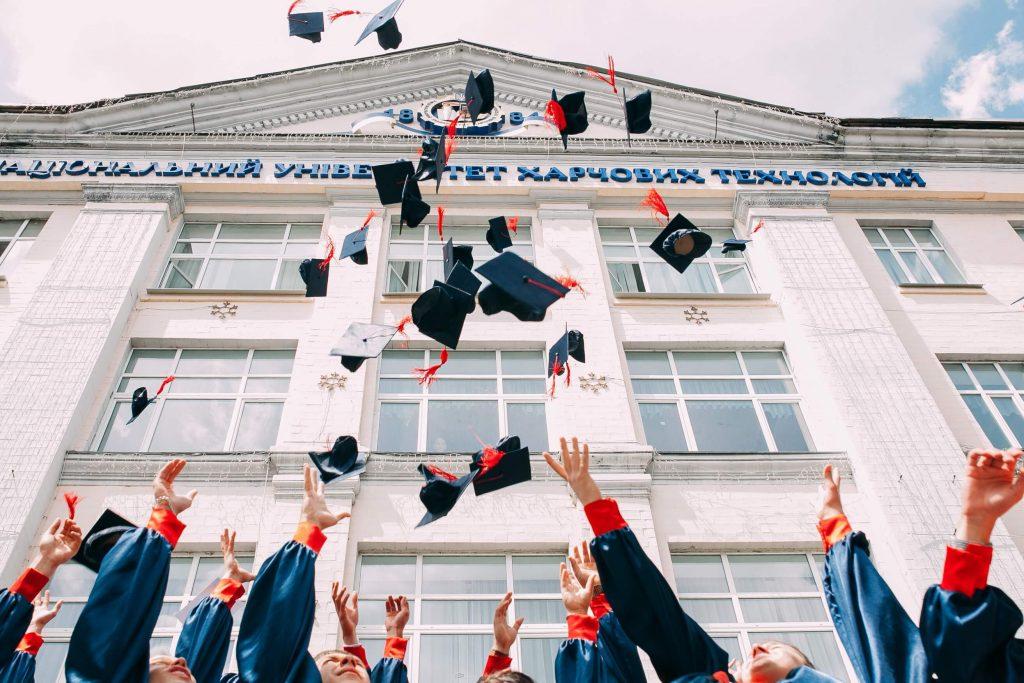 MBA na europa: Formandos universitários vestidos com beca e jogando o capelo para o ar.