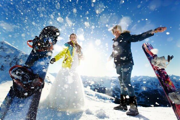 Destinos na América do Sul: Homem e mulher em pés na neve, vestidos para praticar snowboard.