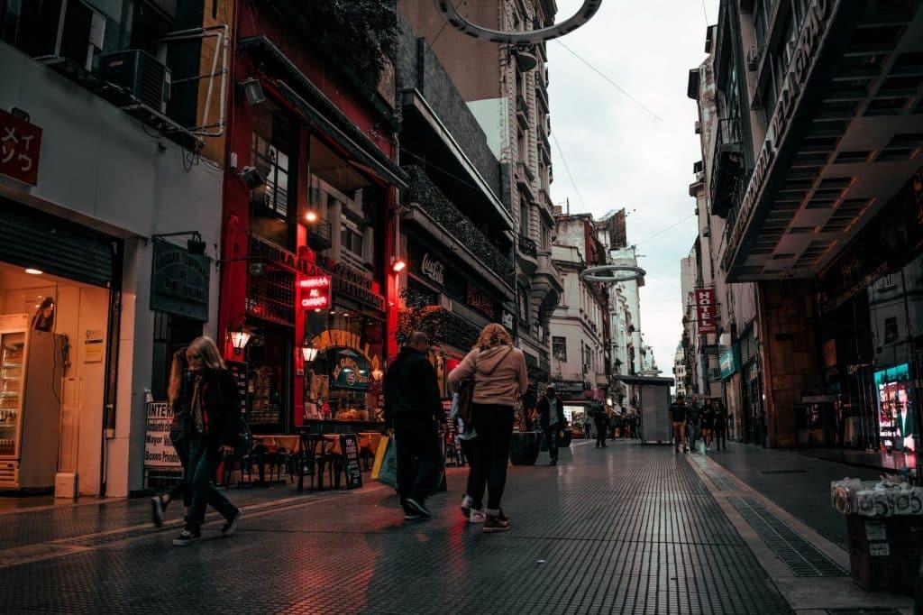 Destinos na América do Sul: Pessoas transitando por uma rua de comércios em Buenos Aires, na Argentina.