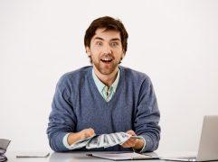 Comissão de afiliados: homem surpreso e animado segurando cédulas de dinheiro