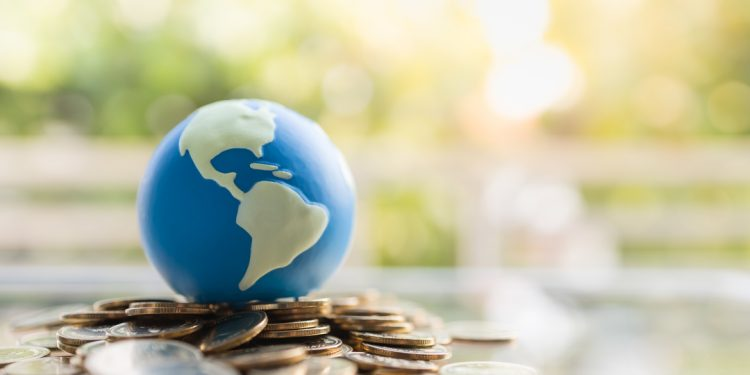Fundos internacionais: mini globo do mundo em pilha de moedas