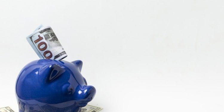 Patrimônio Pessoal: cofrinho de porquinho azul com cédulas de dinheiro
