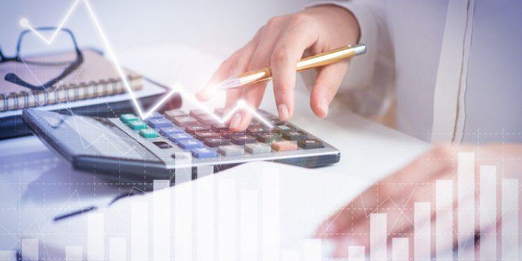 Renda fixa e variável: mulher fazendo cálculos usando a calculadora