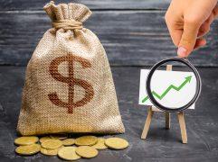 Saco de dinheiro ao lado de lousa com gráfico representando ganho de capital