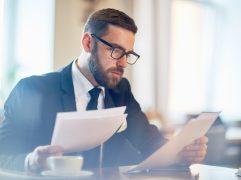 Governança corporativa: homem de negócios lendo documentos empresariais