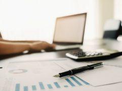 Investir no tesouro direto: homem em mesa de escritório mexendo no notebook