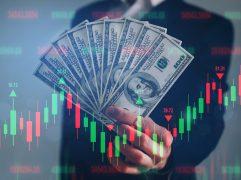 CBOT: homem segurando notas de dolares com gráficos de dados na tela