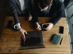Dois homens de negócios apotando para notebook e discutindo sobre competências empreendedoras