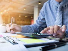 gestão-de-riscos-em-investimentos: homem mexendo em uma calculadora e com uma caneta na outra mão.