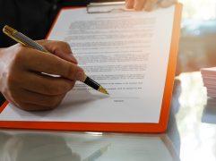 Letter of Acceptance: mão de home assinando documento em prancheta