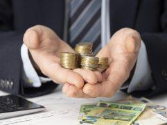 quanto custa um intercâmbio: duas mãos segurando moedas e algumas notas na mesa