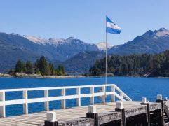 quanto custa uma viagem para argentina: passarela com o mar em volta com a bandeira da argentina