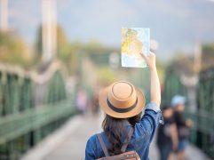 seguro viagem europa: mulher de costas, segurando um mapa.