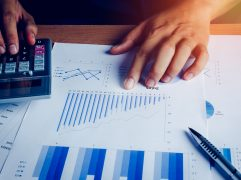 Volatilidade: Mãos sobre papéis com gráficos e calculadora.